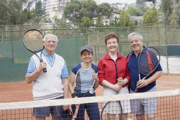 Senior Hispanic couples playing tennis