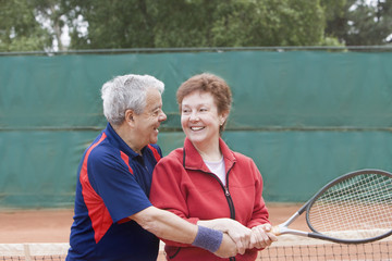 Senior Hispanic man teaching wife to play tennis
