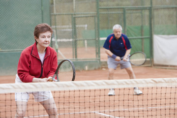 Senior Hispanic couple playing double tennis