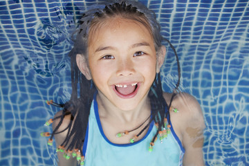 Mixed race girl floating in swimming pool