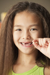 Mixed race girl holding toothy