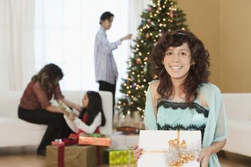 Hispanic girl holding Christmas gift in living room with family