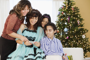 Hispanic family looking at Christmas pictures