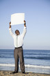 Black businessman standing on beach with blank poster
