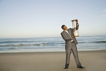 Black businessman standing on beach with large hour glass