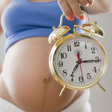 Pregnant Hispanic woman holding alarm clock