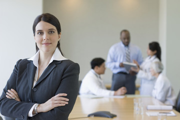 Mixed race businesswoman in conference room with co-workers