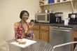 Mixed race businesswoman eating lunch in break room