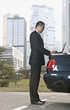 Asian businessman using laptop on car trunk