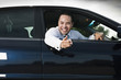Smiling Asian businessman pointing from car