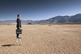 Asian businessman standing on ladder in desert