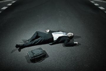 Asian businessman laying on asphalt roadway