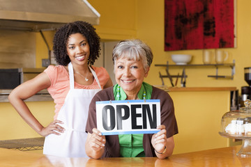 African American business owners in cafe holding open sign