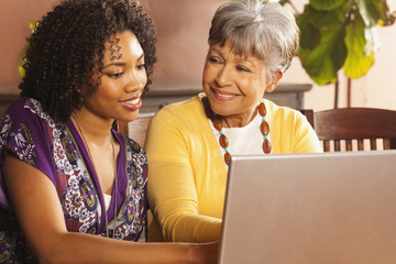African American woman using laptop with her mother