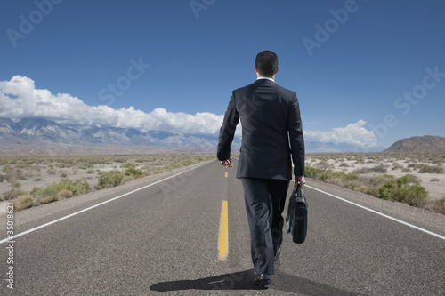 Asian businessman talking on remote highway
