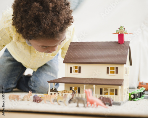 Black boy playing with toy house and animals