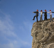 Business people in blindfolds walking off cliff