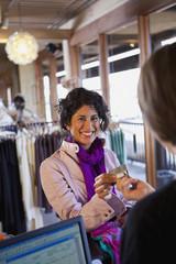 Ecuadorian woman handing credit card to clerk in clothing shop