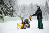 A man operating snow blower in winter