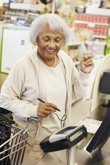 Senior African American woman paying with credit card in grocery store