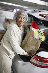 Senior African American woman putting groceries into trunk of car