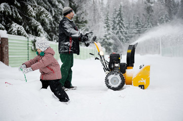Young father operates snow blower in winter