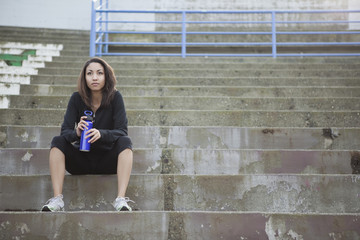 Mixed race woman with water bottle sitting in stadium