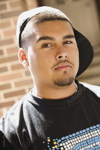 Serious Hispanic man wearing cap