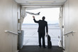 Hispanic businessman standing on jetway waving