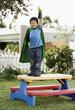 Korean boy in superhero costume with arm raised