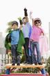 Korean children in superhero costumes with arms raised