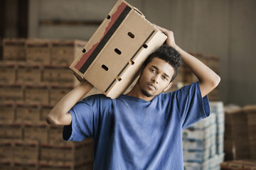 Mixed race man carrying cardboard box in warehouse