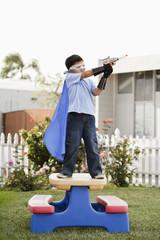 Korean boy in superhero costume aiming gun