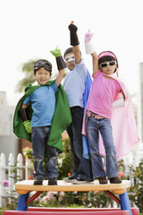 Korean children in superhero costumes with arms raised