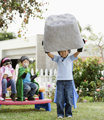 Korean boy as superheros lifting large boulder