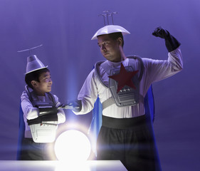 Korean boy and father in superhero costumes looking at glowing orb