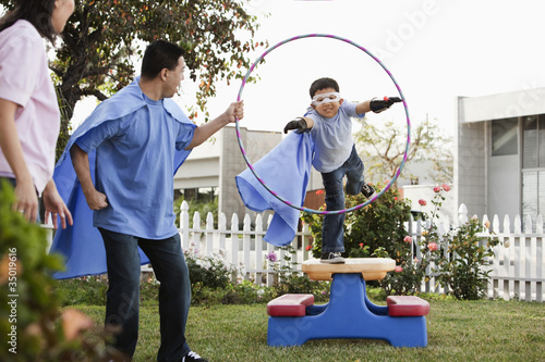 Korean boy in superhero costume jumping through hoop