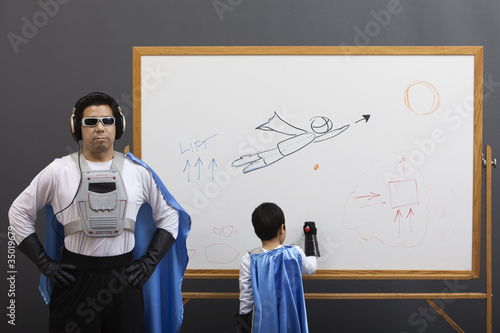 Asian superhero family looking at whiteboard