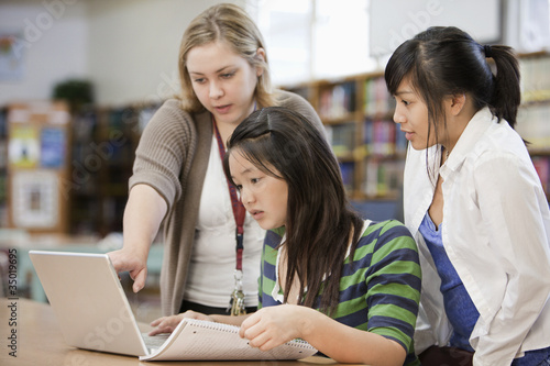 Librarian helping students with research in school library