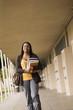 Student carrying books in school corridor