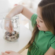 Mixed race girl taking coin out of jar