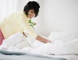 Hispanic woman making bed