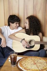 Girlfriend playing guitar for boyfriend