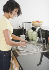 Hispanic woman washing pan in kitchen