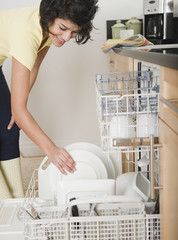 Hispanic woman putting dishes in dishwasher