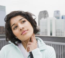 Hispanic woman checking pulse in city