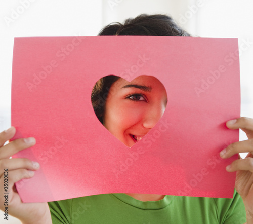 Hispanic woman looking through heart-shaped hole