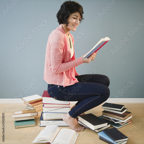 Hispanic woman reading books