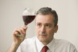 Caucasian businessman looking at glass of red wine