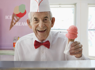 Senior Hispanic man serving ice cream